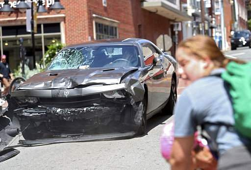 A vehicle reverses after driving into a group of protesters demonstrating against a white nationalist rally in Charlottesville, Va., Saturday, Aug. 12, 2017. The nationalists were holding the rally to protest plans by the city of Charlottesville to remove a statue of Confederate Gen. Robert E. Lee. There were several hundred protesters marching in a long line when the car drove into a group of them.|AP