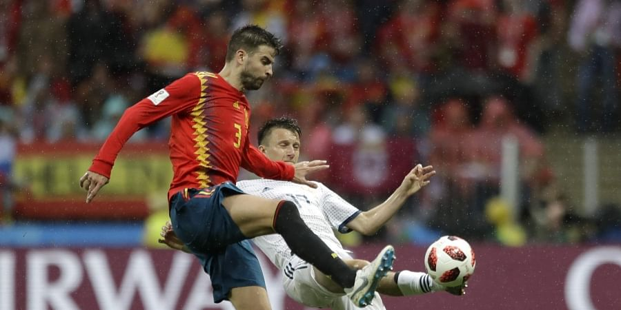 Spain's Gerard Pique, left, and Russia's Alexander Golovin battle for the ball. (Photo | AP)