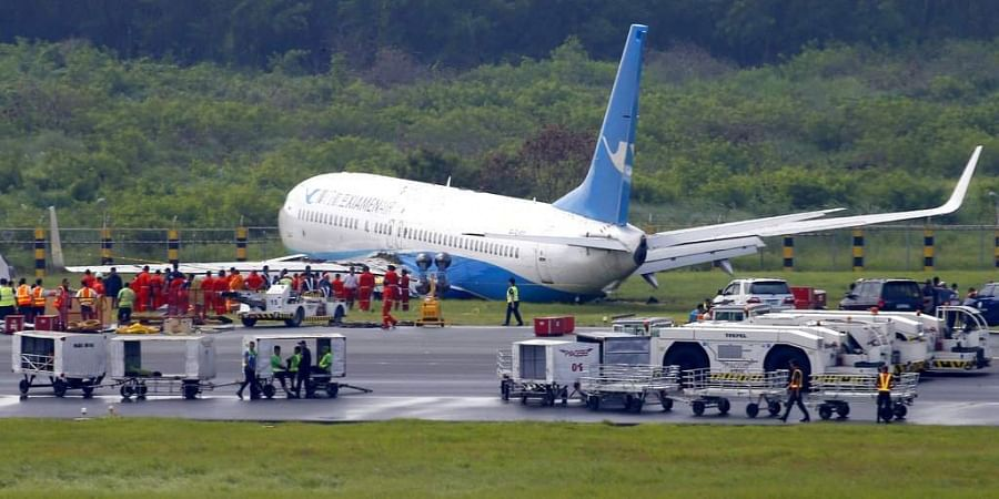 A Boeing passenger plane from China, a Xiamen Air, sits on the grassy portion of the runway of the Ninoy Aquino International Airport after it skidded off the runway while landing Friday, Aug. 17, 2018 in suburban Pasay city southeast of Manila, Philippin