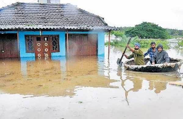 Two men being moved to safer ground by a coracle on Graveyard Road in Koppa of Kodagu district on Friday | Udayashankar S