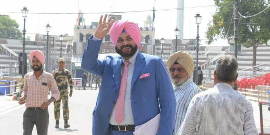 Former Indian cricketer-turned-politician and Punjab Cabinet Minister Navjot Singh Sidhu (C) gestures as he crosses the India Pakistan border in Wagah. (Photo | AFP)