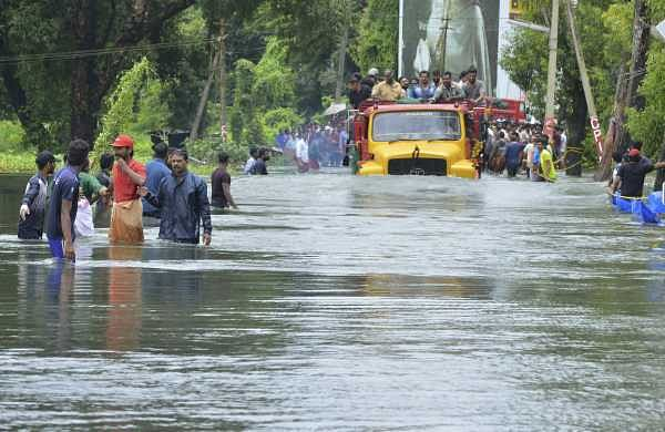 A truck carries people past a flooded road in Thrissur, Kerala. (Photo | AP)