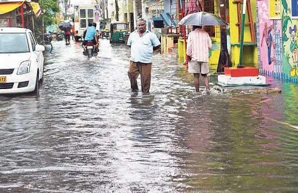 People wade through water in Rotary Nagar