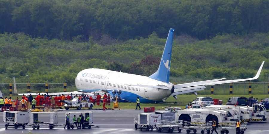 A Boeing passenger plane from China, a Xiamen Air, sits on the grassy portion of the runway of the Ninoy Aquino International Airport after it skidded off the runway while landing Friday, Aug. 17, 2018 in suburban Pasay city southeast of Manila, Philippines. (Photo | AP)