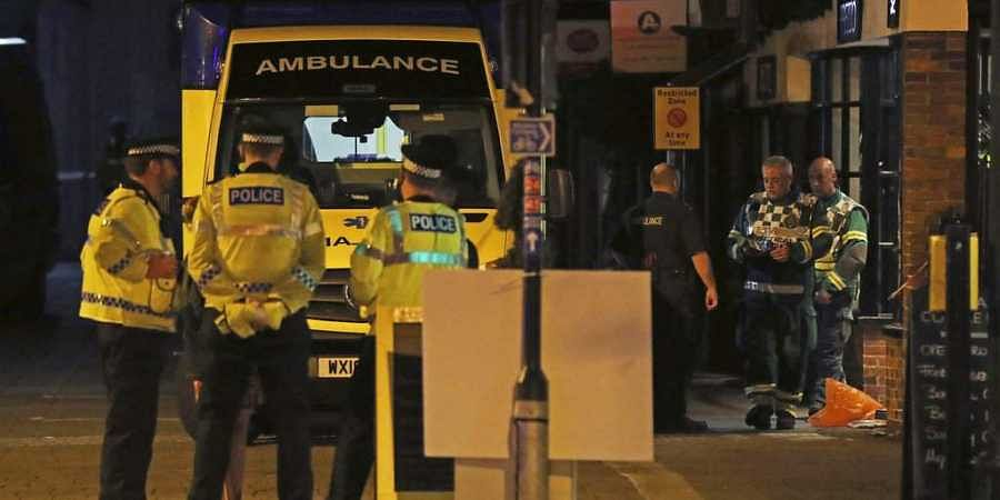 Emergency services personnel stage outside Prezzo restaurant, Sunday, Sept. 16, 2018, in Salisbury, United Kingdom, where police have closed streets as a 'precautionary measure' after two people were taken ill from the restaurant, amid heightened tensions