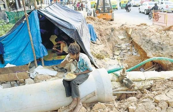 Workers pitch a tent on an ongoing drainage pipe laying work which has been delayed for many months, near Someshwarapura, in Bengaluru | Pandarinath B
