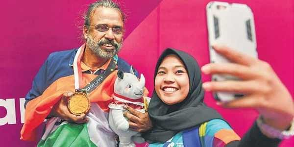 Shibhnath Sarkar poses for a selfie with a volunteer after winning gold in men's pair bridge competition in Jakarta on Saturday | PTI