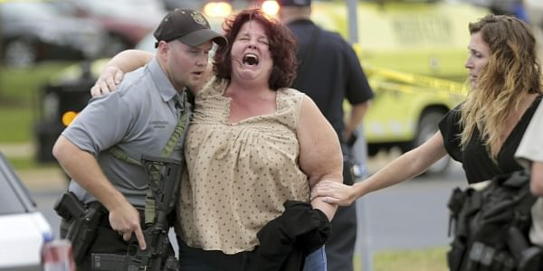 A woman is escorted from the scene of a shooting at a software company in Middleton. (Photo | AP)