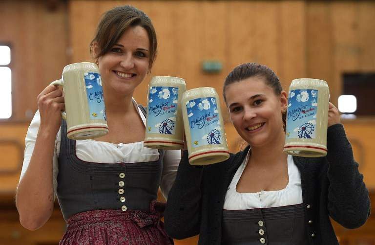 Women wearing traditional Bavarian dirndl pose with the new Oktoberfest beer mugs after a press conference at the Oktoberfest grounds in Munich. (Photo | AFP)