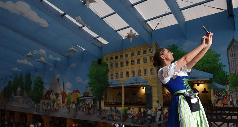 A German waitress takes a selfie as the first visitors arrive to book tables before the official opening of the 185th Oktoberfest, Munich's annual beer festival, on September 22, 2018 in Munich, southern Germany. (Photo | AFP)
