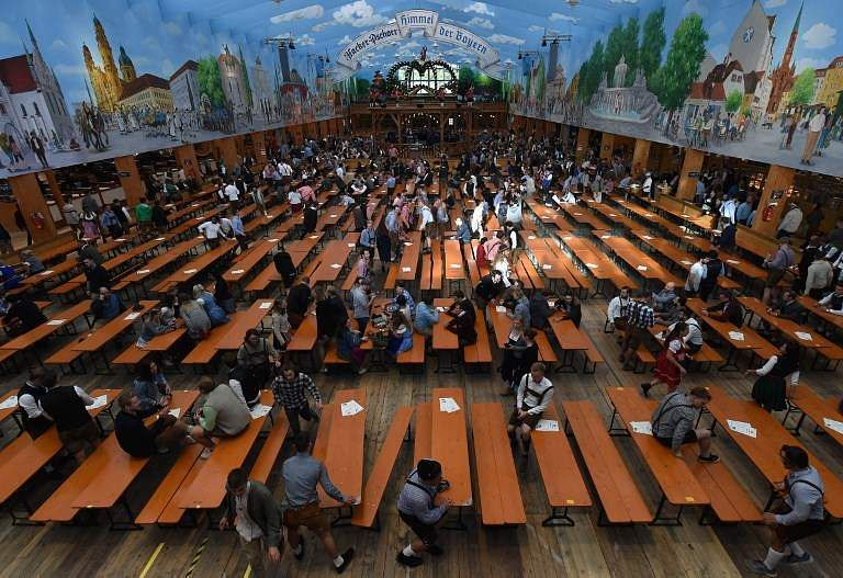 First visitors book tables inside a tent before the official opening of the 185th Oktoberfest, Munich's annual beer festival, on September 22, 2018 in Munich, southern Germany. The world's largest beer festival is held from September 22 until October 7, 2018.  (Photo | AFP)
