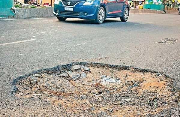 A pothole-ridden road near Ulsoor on Sunday; (below) workers undertake asphasting work on a road | Pandarinath B