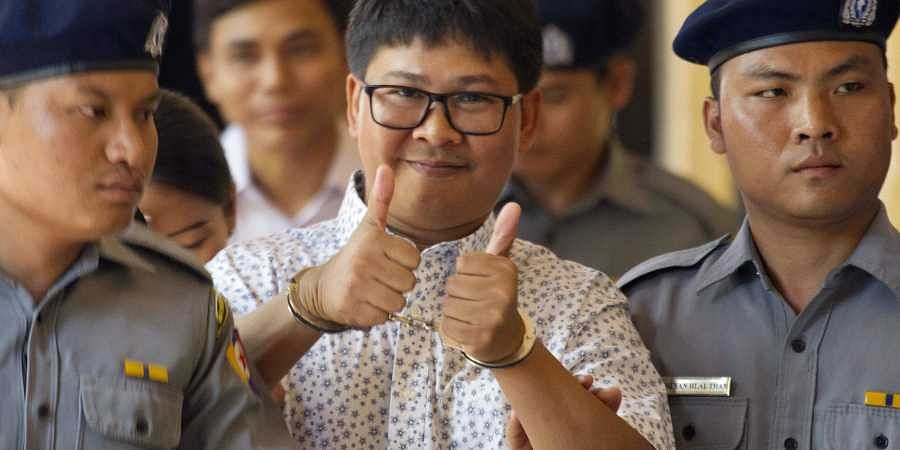 Reuters journalist Wa Lone, center, thumbs up as he is escorted by police upon arrival at the court for trial in Yangon, Myanmar Friday, April 20, 2018. | AP