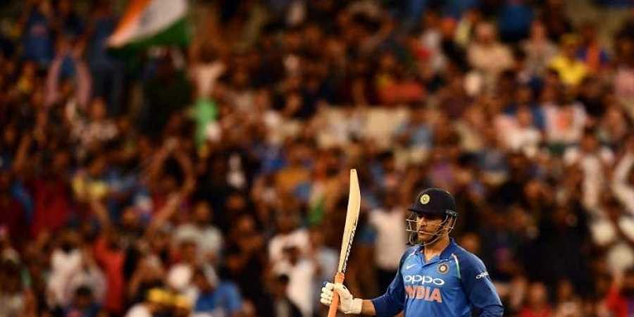 India's Mahendra Singh Dhoni rises his bat after scoring a half-century (50 runs) during the third one-day international cricket match between Australia and India at the Melbourne Cricket Ground in Melbourne. (Photo | AFP)