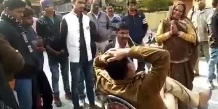 woman touching feet of UP police inspector