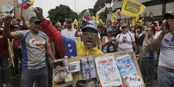 An opposition member holds a poster board with the prices of basic food during a protest against Venezuela's President Nicolas Maduro in Caracas, Venezuela, Wednesday, Jan. 23, 2019. (Photo: AP)
