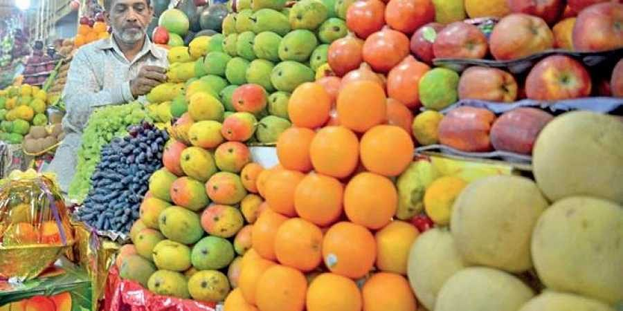 A vendor arranges fruits at his stall.