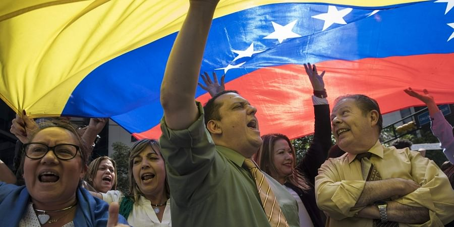 People chant 'Free elections' in a walk out against President Nicolas Maduro, in the financial district of Caracas, Venezuela. (Photo | AP)