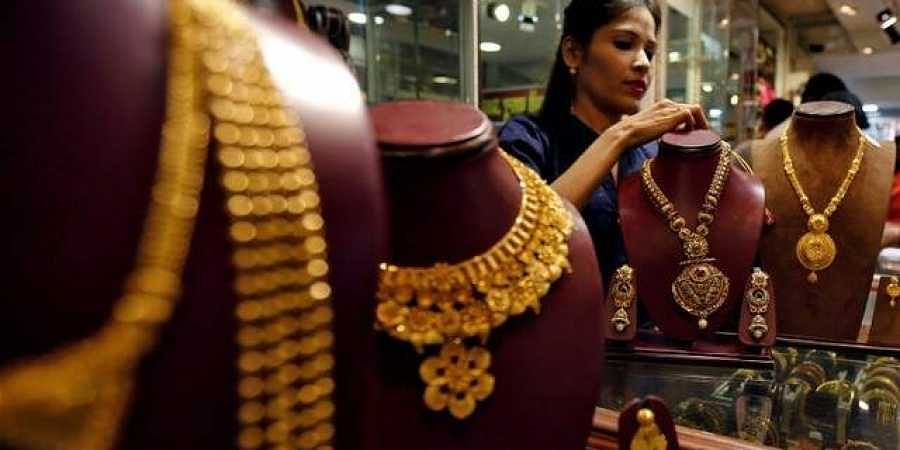 A salesperson attends to a customer (not pictured) inside a jewellery showroom, during Akshaya Tritiya, a major gold-buying festival, in Mumbai. (Photo | REUTERS)