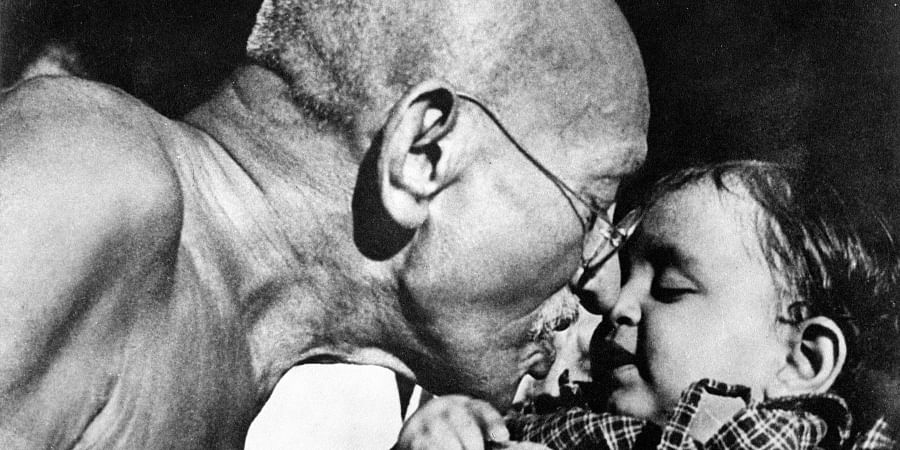Gandhiji seen here playing with a tot.