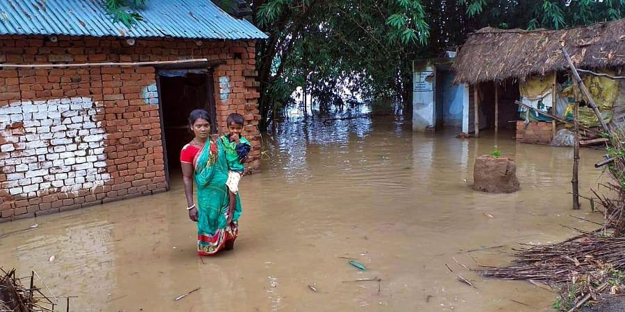 A villager carrying a child stands in front of her house in a waterlogged area following overflow of Dwarka river at Tetulberia village in Birbhum Monday Sept. 30 2019. | (Photo | PTI)