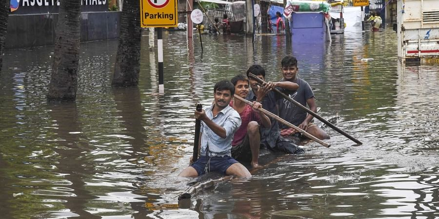 Residents row a makeshift boat to cross a flood-affected area following heavy monsoon rainfall in Patna. (Photo | PTI)