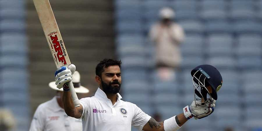 Indian cricketer Virat Kohli celebrates after scoring a century during the second day of the second cricket test match between India and South Africa in Pune, India.
