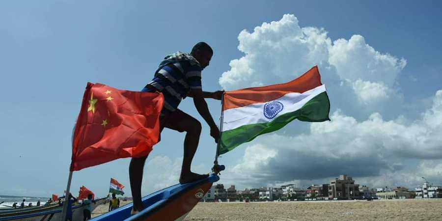 Fishermen's at Palavakkam beach tie two national flags on their boats in welcoming the Chinese president and Indian Prime Minister to Chennai on Thursday