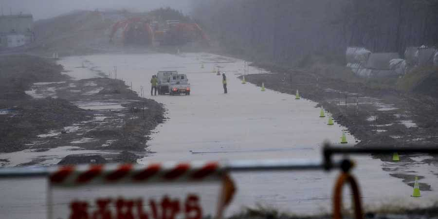 Workmen stand on a flooded road in Hamamatsu, Japan