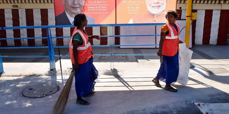 Corporation workers clean footpath and roads at OMR by which Narendra Modi and Chinese President Xi Jinping will go to Mahabalipuram from the city for two days meet. | (Photo | Debdutta Mallick/EPS)