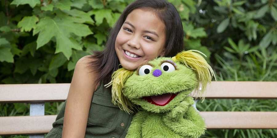 This undated image released by Sesame Workshop shows 10-year-old Salia Woodbury, whose parents are in recovery, with 'Sesame Street' character Karli. (Photo | AP)