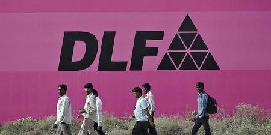 Workers walk past a billboard of DLF Ltd. at Gurgaon in the outskirts of New Delhi