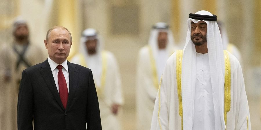 Russian President Vladimir Putin, left, and Abu Dhabi Crown Prince Mohamed bin Zayed al-Nahyan listen to the national anthem during the official welcome ceremony in Abu Dhabi, United Arab Emirates. (Photo | AP)