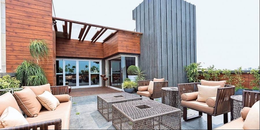 With the bungalow rising imposingly in the background, this terrace space is dotted with potted plants and luxurious seating options.