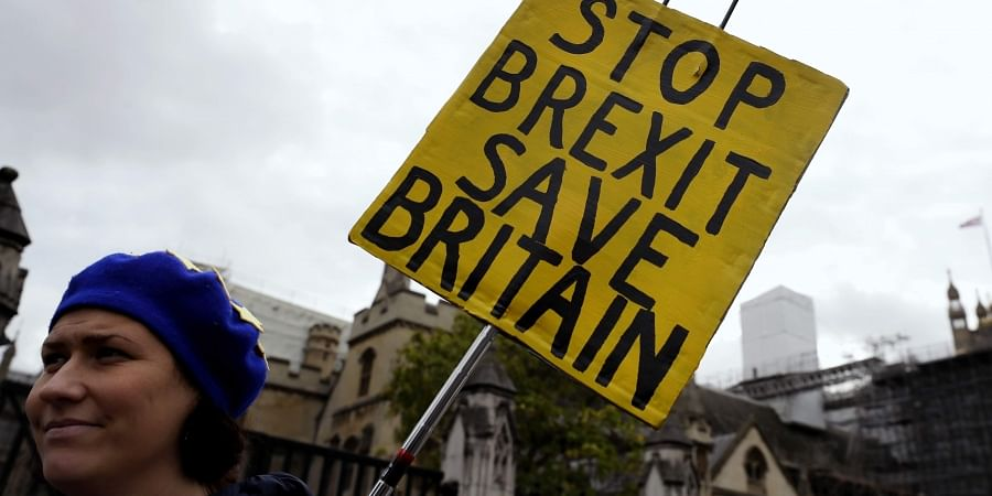 An anti-Brexit campaigner holds a banner near Parliament in London.