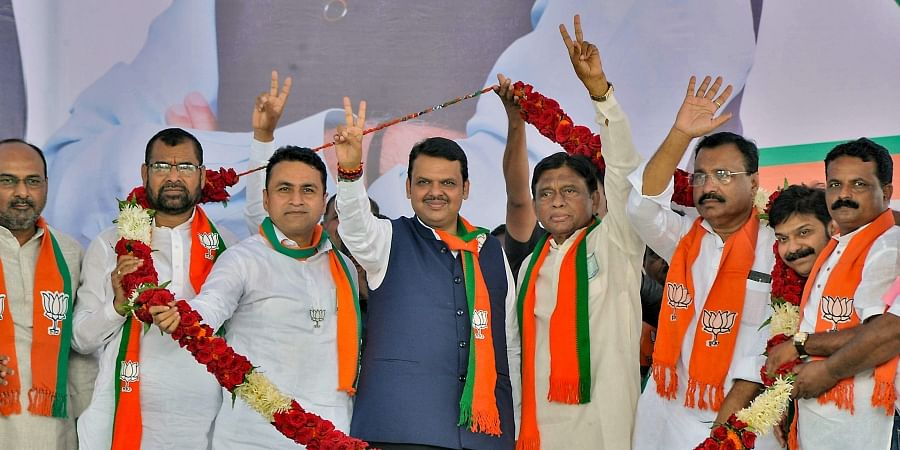 Maharashtra Chief Minister Devendra Fadnavis with BJP's Shiral constituency candidate Shivajirao Naik and others being garlanded in a campaign rally ahead of Maharashtra Assembly elections at Kameri in Sangli Tuesday Oct. 15 2019. | (Photo | PTI)