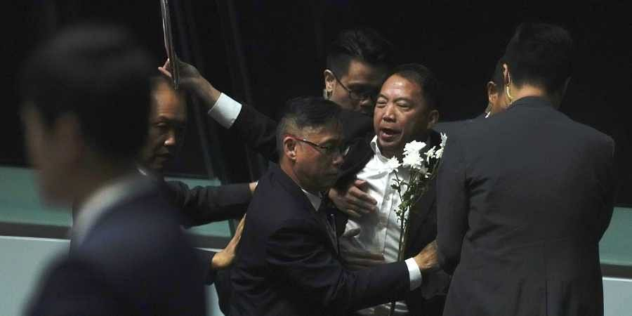 A pro-democracy lawmaker is taken away as he shouts a slogan while Hong Kong Chief Executive Carrie Lam arrives at chamber of the Legislative Council in Hong Kong