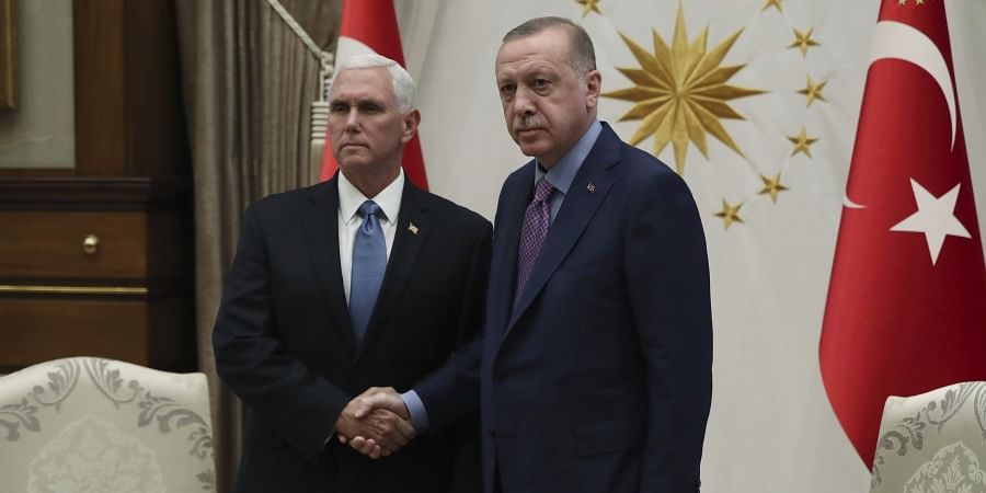 Turkish President Recep Tayyip Erdogan (R) shakes hands with US Vice President Mike Pence, prior to their talks at the Presidential Palace in Ankara, Turkey