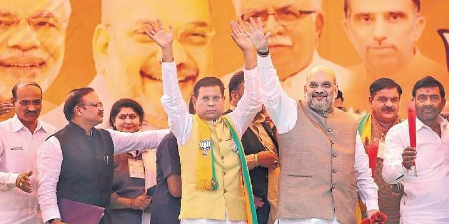 Union Home Minister Amit Shah waves at the crowd during an election campaign rally, ahead of Haryana Assembly elections, in Faridabad on Wednesday.