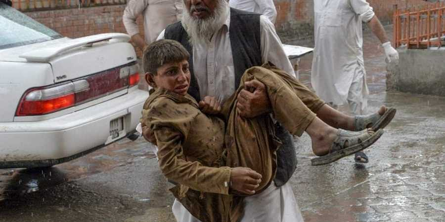 A volunteer carries an injured youth to hospital, following a bomb blast in Haska Mina district of Nangarhar Province on October 18, 2019.