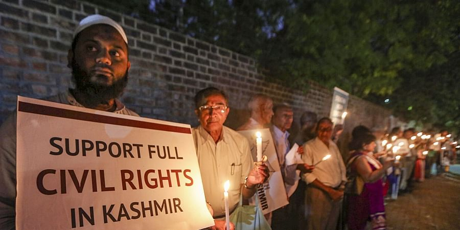Social activists hold a placard and candles during a silent protest against government on Kashmir issue in Ahmedabad Thursday Oct. 17 2019. | (Photo | PTI)