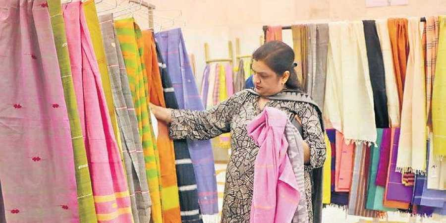A customer viewing saris exhibited at the RK Khanna Stadium.