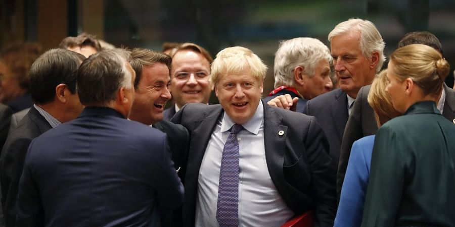 British Prime Minister Boris Johnson, center, is greeted by Luxembourg's Prime Minister Xavier Bettel, center left, during a round table meeting at an EU summit in Brussels.