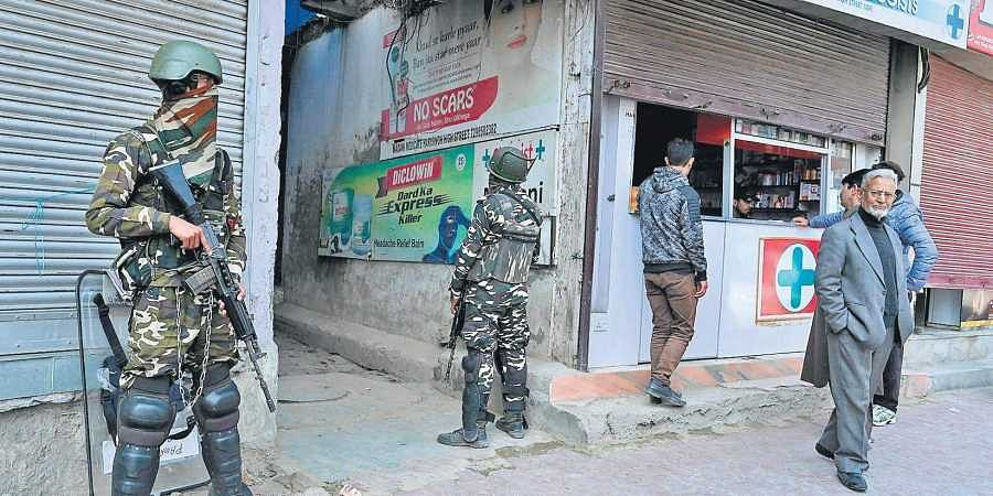 Troopers stand guard outside a chemist in Srinagar. Security has been enhanced a day after two men were killed in Kashmir