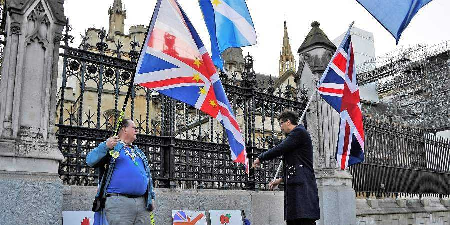 A pro-Brexit supporter, left, and an anti-Brexit supporter, right, talk outside the Houses of Parliament in London.