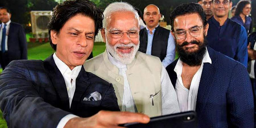 PM Narendra Modi poses for a selfie with Bollywood actors Shah Rukh Khan and Aamir Khan at an event to mark Mahatma Gandhi's 150th birth anniversary year in New Delhi.