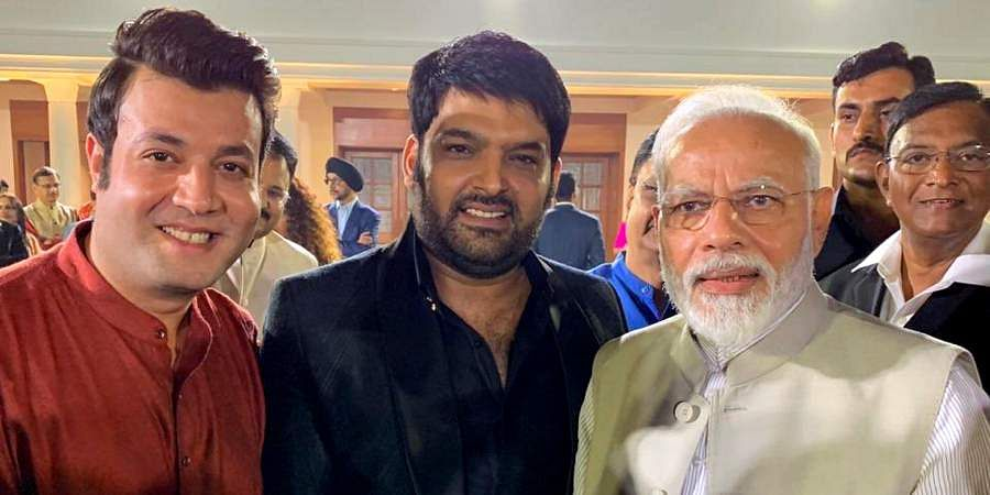 PM Narendra Modi poses for a photo with comedian Kapil Shamra and actor Varun Sharma at an event to mark Mahatma Gandhi's 150th birth anniversary year in New Delhi.