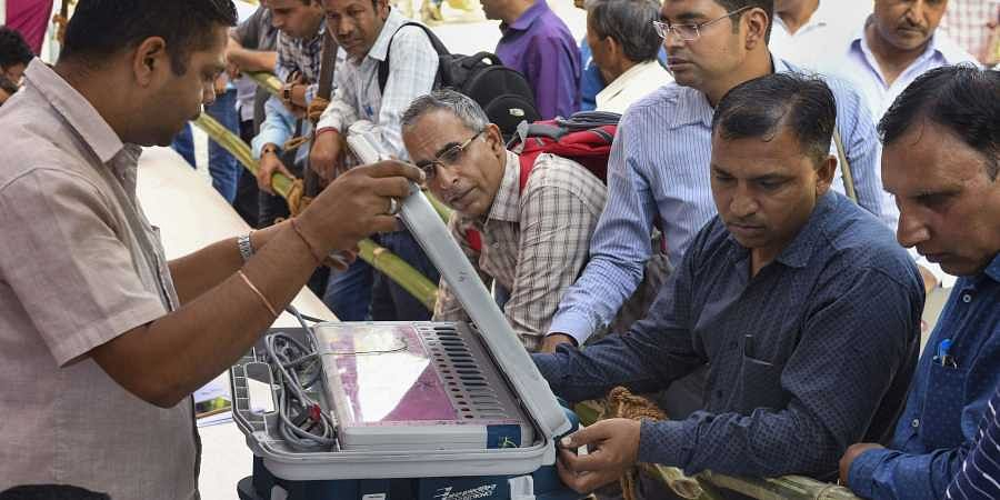 Poll officials collect EVMs and other election materials from a distribution centre on the eve of Haryana Assembly polls in Panchkula Sunday Oct. 20 2019.
