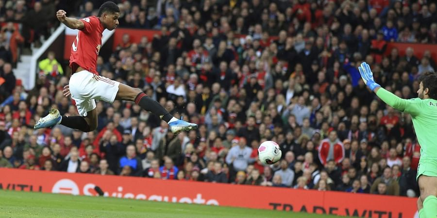 Manchester United's Marcus Rashford scores his side's opening goal against Liverpool at the Old Trafford stadium in Manchester.