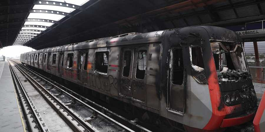 Subway cars burnt by protesters are parked at the Elisa Correa station in Santiago, Chile.
